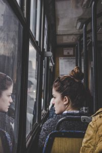 Woman looking at her reflection in bus window