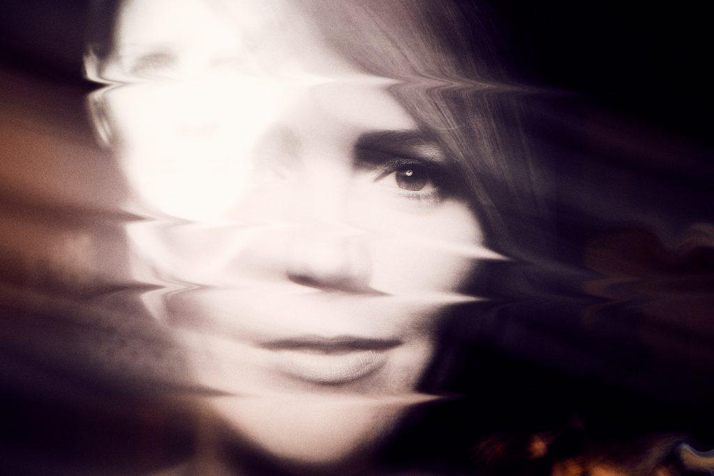 Woman's face seen through blurry lens
